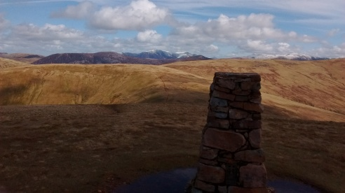 Lank Rigg trig point with Whoap in the foreground and the snow covered central fells behind 4